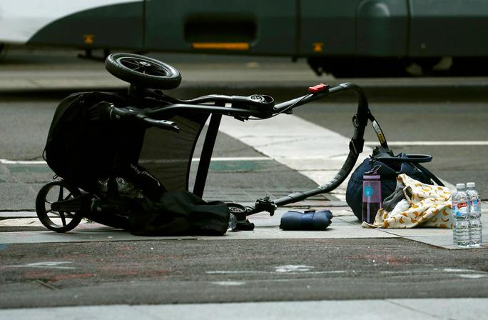 Chiếc xe đẩy trẻ em bị kéo lê trên đường. Ảnh: Reuters