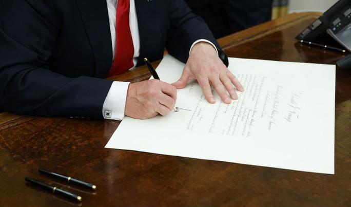 Tân Tổng thống Mỹ Donald Trump đã ký những giấy tờ đầu tiên tại phòng Bầu dục. Ảnh: AP