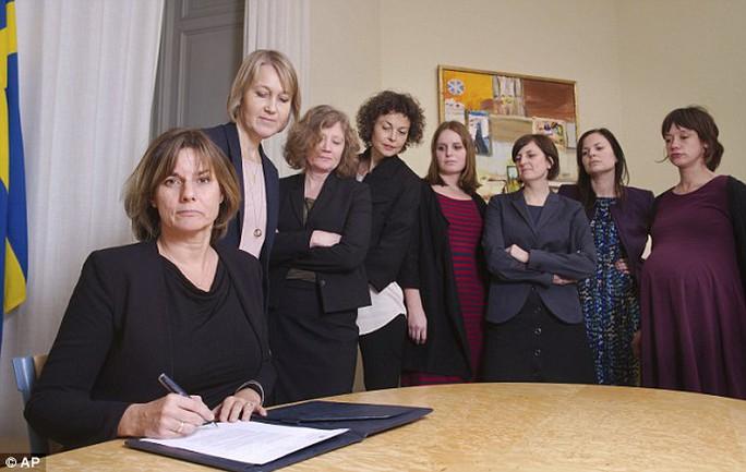 Phó thủ tướng Thụy Điển ký kết văn bản về biến đổi khí hậu, xung quanh bà là các thành viên chính phủ. Ảnh: AP