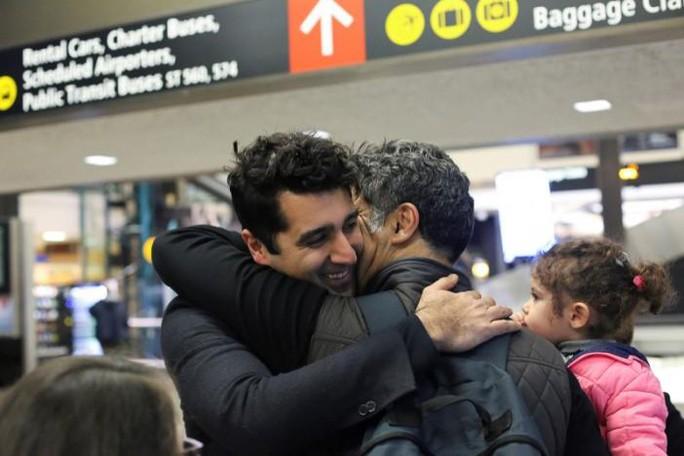 Cyrus Khosravi - một công dân Iran có thẻ xanh Mỹ (trái) ôm anh trai Hamidreza Khosravi đang bế cô cháu gái Dena Khosravisau khi hai cha con bị giữ lại kiểm tra ở sân bay sau khi đến sân bay quốc tế Seattle-Tacoma để thăm Cyrushôm 6-2-2017. Ảnh: Reuters