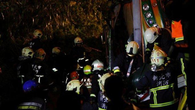 Lực lượng cứu hộ cố gắng giải thoát nạn nhân trong xe. Ảnh: Reuters