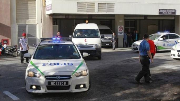 Một xe tải nhỏ rời bệnh viện Putrajaya ở Kuala Lumpur sáng 15-2 với sự hộ tống của cảnh sát. Ảnh: AP