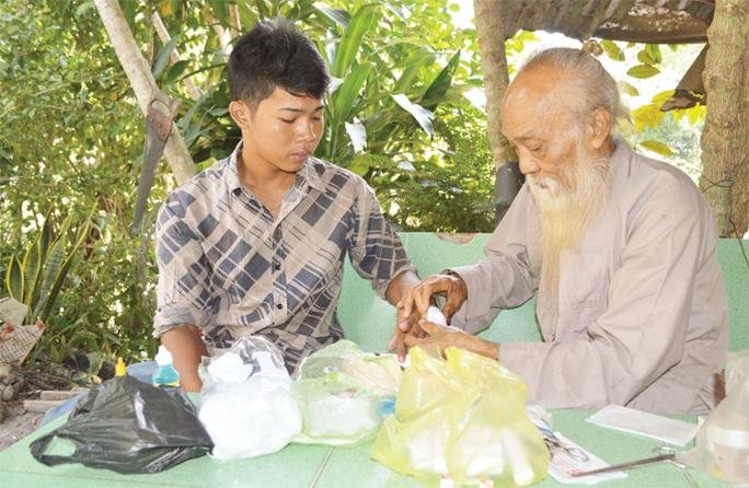 Ông Tư Đền bó thuốc cho anh Chau Rit