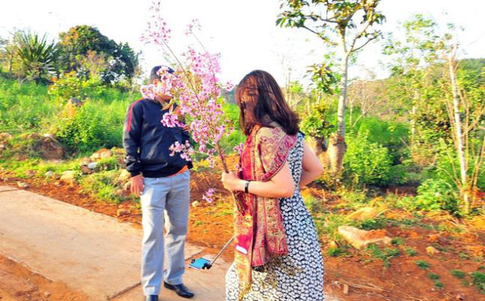 Ảnh bà Hiếu cầm nhành hoa anh đào để chụp ảnh (ảnh Facebook N.A.T)