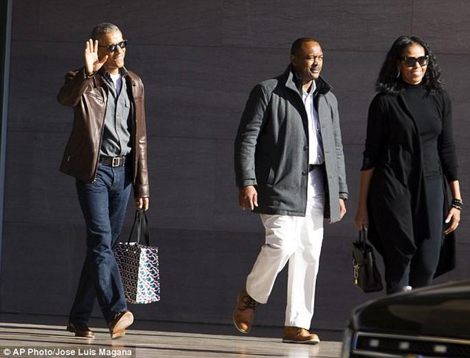 Vợ chồng cựu Tổng thống Obama mỉm cười với phóng viên khi họ rời khỏi Bảo tàng Nghệ thuận quốc gia ở thủ đô Washington hôm 5-2. Ảnh: AP