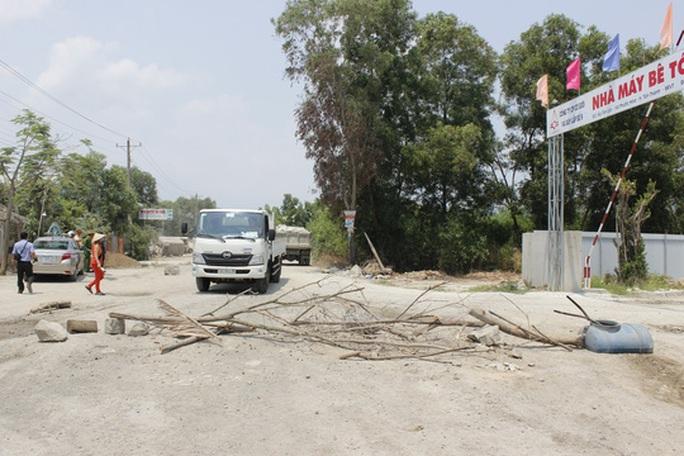Người dân mang đá, cành cây ra chắn đường các xe tải chở đá