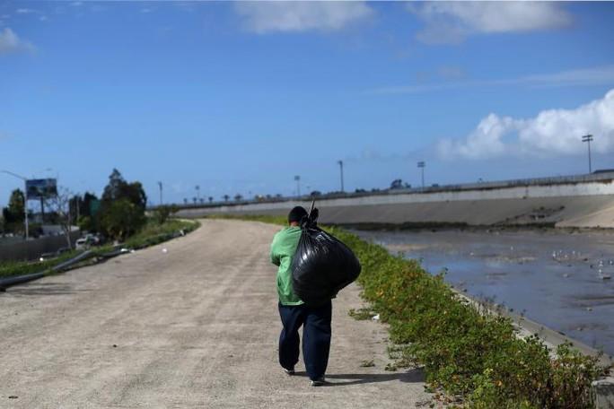 Một người Mexico bị trục xuất khỏi Mỹ khệ nệ vác đồ gần sông Tijuana, Mexico, ngày 22-2. Ảnh: REUTERS