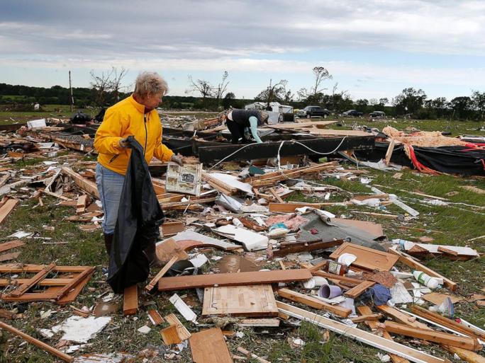 Một phụ nữ thu nhặt đồ đạc sau khi cơn bão phá hủy nhà của bà ở bang Texas. Ảnh: EPA