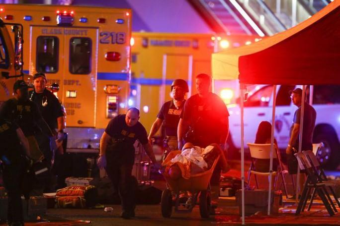 Một nạn nhân được đưa đi cấp cứu giữa lúc cảnh sát đang xử lý tại hiện trường. Ảnh: AP