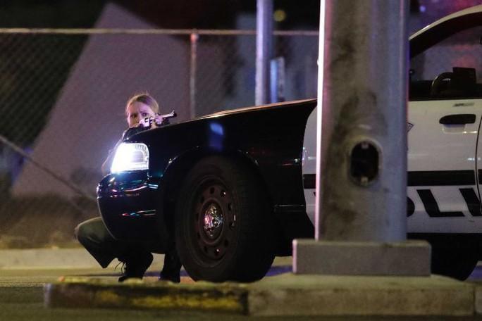 Một nữ cảnh sát nấp sau xe cảnh sát gần hiện trường. Ảnh: AP