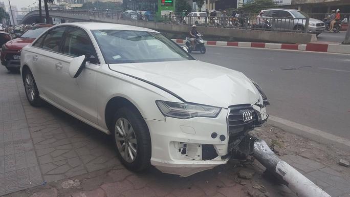 Xế hộp Audi lao lên vỉa hè tông cột đèn đổ trúng đầu người đi đường - Ảnh 1.