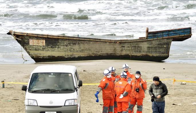 Các nhân viên thuộc lực lượng bảo vệ bờ biển Nhật Bản đứng gần con tàu trôi dạt vào bờ biển tỉnh Akita. Ảnh: Kyodo