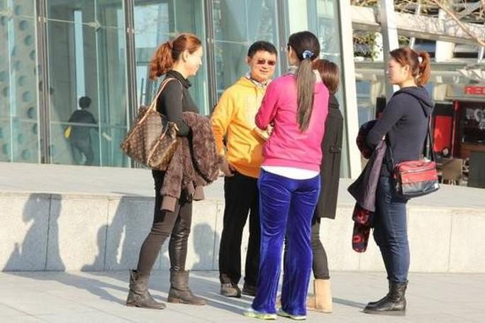 Ông Tiêu trò chuyện với nữ vệ sĩ, trợ lý tại lối vào khách sạn Ảnh: NTDTV