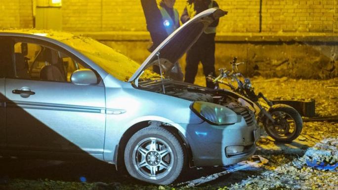 Chiếc xe máy cháy đen nằm cạnh xe hơi. Ảnh: Reuters