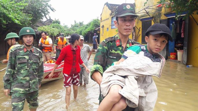 Bộ đội dùng ca nô vượt lũ đưa người đi cấp cứu - Ảnh 1.