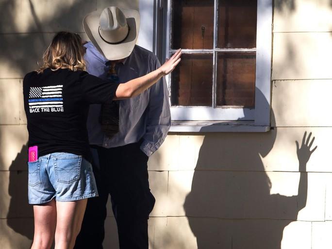 Một phụ nữ và một người đàn ông cầu nguyện sau vụ xả súng. Ảnh: Stateman.com