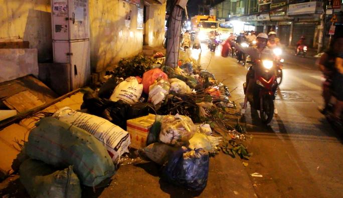 Đường Nguyễn Văn Nghi (quận Gò Vấp) dài hơn 1 km nhưng có cả chục đống rác tự phát (ảnh chụp tại một bãi rác tự phát trên tuyến đường này khoảng 20 giờ ngày 3-5, nhiều người xách từng bọc rác lớn vứt xuống rồi bỏ đi)