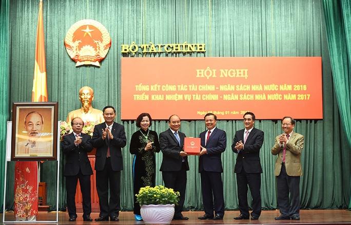 Thủ tướng Nguyễn Xuân Phúc tặng quà lưu niệm cho Bộ Tài chính - Ảnh: Quang Hiếu