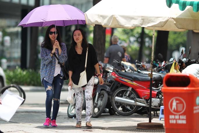 Nhiều du khách khi đi dạo phải mang theo dù dưới cái nắng chói chang ...
