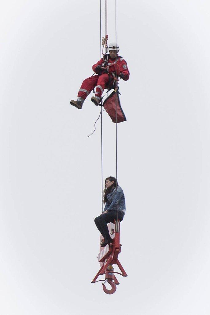 Cô gái ngồi đung đưa trên phần ròng rọc của cần cẩu. Ảnh: National Post