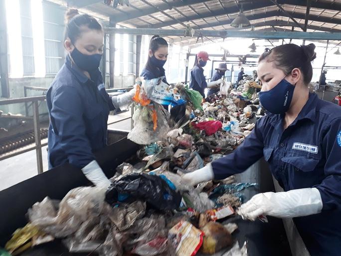 Công nhân phân loại rác tại một nhà máy xử lý rác thải đóng tại Bình Dương