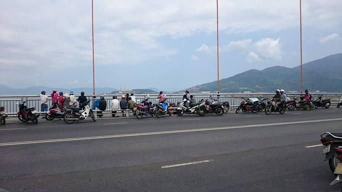 Người nhà nạn nhân chờ lực lượng cứu hộ tìm kiếm thi thể của N. tại cầu Thuận Phước