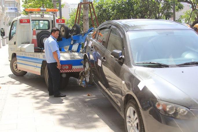Ô tô đậu trên vỉa hè đường Nguyễn Huệ bị cẩu đi