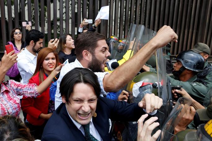 Phe đối lập xô xát với vệ binh quốc gia bên ngoài Tòa án Tối cao Venezuela hôm 30-3 Ảnh: REUTERS