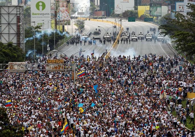Những người chống đối đụng độ với cảnh sát ở Caracas hôm 19-4 Ảnh: REUTERS