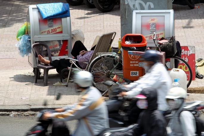Trên vỉa hè đường Trần Hưng Đạo (quận 1), một người bán hàng rong không còn sức để mua bán khi ngoài trời nắng như đổ lửa