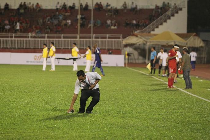 Một thành viên BTC sân vào nhặt chai nước mà tiền vệ Hồng Việt ném xuống để phản ứng HLV Alain Fiard