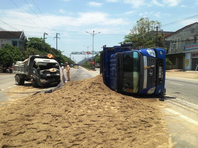 Hiện trường vụ tai nạn khiến một chiếc xe tải nằm lật nghiêng giữa đường