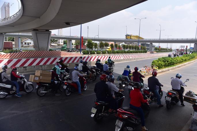 Nhiều người chạy xe máy dừng đèn đỏ dưới gầm cầu vượt Cát Lái (quận 2) để tránh nắng nóng thay vì phải dừng ở vị trí đèn xanh đèn đỏ phía trước.