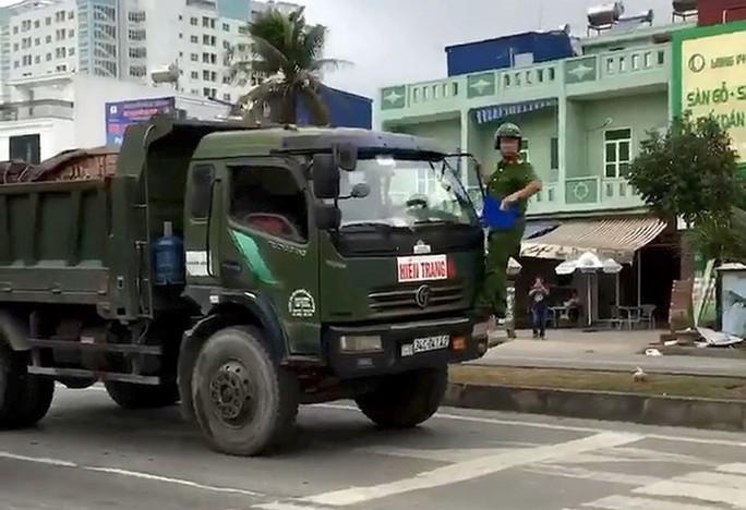 Cảnh sát phải đánh đu trên đầu xe tải - Ảnh 1.