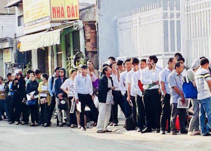 Người dân xếp hàng dài ra đường chờ làm thủ tục nhà đất tại UBND quận 9 - Ảnh 1.