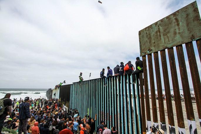 Người di cư trèo lên hàng rào biên giới Mỹ - Mexico - Ảnh 1.