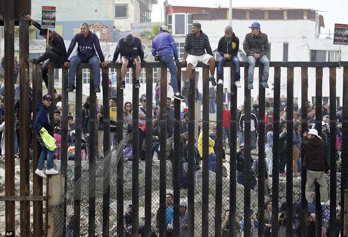 Người di cư trèo lên hàng rào biên giới Mỹ - Mexico - Ảnh 3.