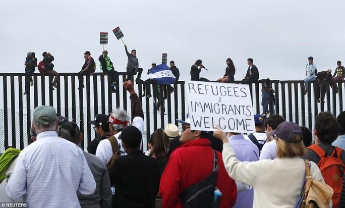 Người di cư trèo lên hàng rào biên giới Mỹ - Mexico - Ảnh 4.
