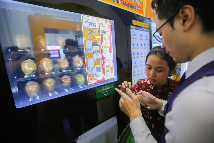 Người Sài Gòn thích thú với máy bán dừa tự động độc đáo - Ảnh 3.