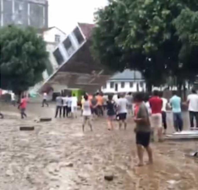 Khủng khiếp cảnh nhà 6 tầng bị mưa lũ kéo đổ trong chớp mắt ở Trung Quốc - Ảnh 1.