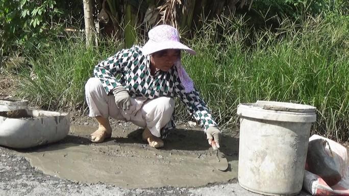 Người phụ nữ nghèo hơn 10 năm bỏ tiền túi vá đường - Ảnh 2.