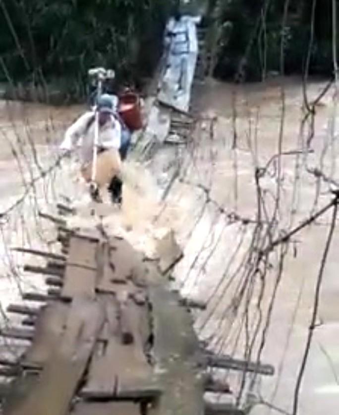 Thót tim trước cảnh mạo hiểm vượt nước lũ bằng cầu treo - Ảnh 1.