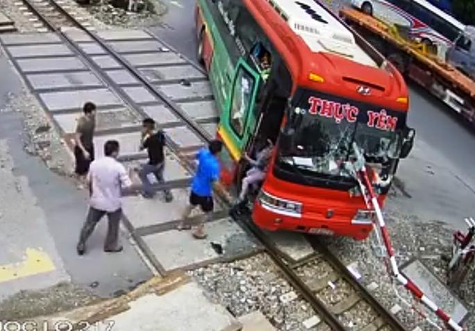 Video: Xe khách tông gãy gác chắn khi tàu hỏa lao tới, hành khách hoảng loạn - Ảnh 2.