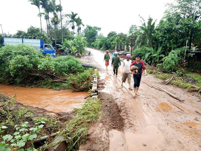 Chạy xe máy qua vùng nước lũ, 2 thanh niên bị cuốn trôi - Ảnh 1.