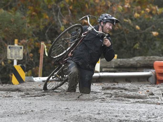Một người đàn ông vác xe đạp trên một con đường ngập bùn ở khu vực Carpinteria. Ảnh: AP