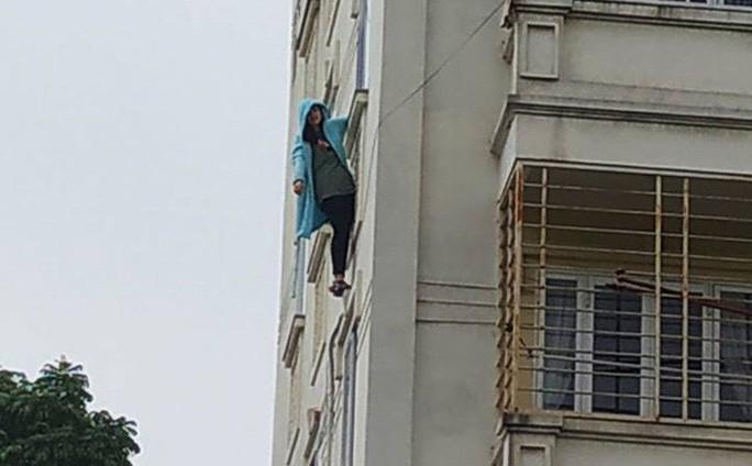 Cô gái trẻ bất ngờ đu mình ra ngoài cửa sổ chung cư rồi nhờ gọi cảnh sát giải cứu - Ảnh 1.