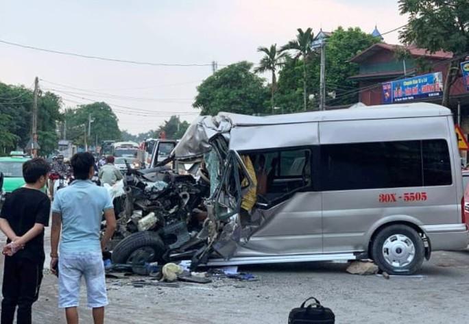 Ôtô 16 chỗ nát đầu khi tông xe tải, 2 tài xế nhập viện cấp cứu - Ảnh 1.