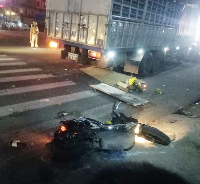 Xe tải biển nước ngoài tông xe máy dừng chờ đèn đỏ, vợ tử vong, chồng trọng thương - Ảnh 1.
