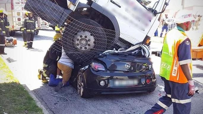 Ngồi trong xe hơi, bị xe tải đè bẹp rúm không chết - Ảnh 1.