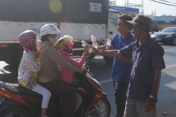 CSGT Đồng Tháp phát nước, khăn lạnh cho người dân trên đường về quê ăn Tết - Ảnh 2.